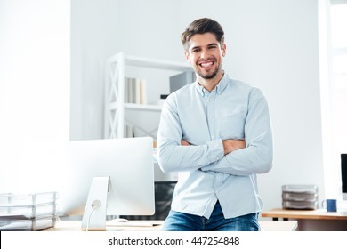 Happy confident young businessman standing with arms crossed in office