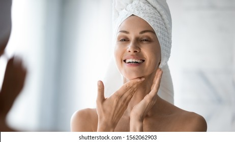 Happy confident young lady with towel on head look in bathroom mirror touching moisturized soft healthy sensitive skin doing morning hydration spa beauty routine, facial skincare treatment concept