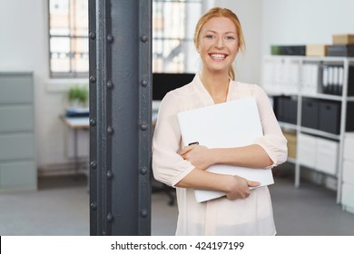 Happy confident young redhead businesswoman standing clutching paperwork and leaning against a pillar in the office giving the camera a beaming friendly smile