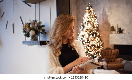 Happy and confident young woman at home plans goals for the new year. New year's resolutions. the background of an apartment with a decorated Christmas tree. Soft style image
