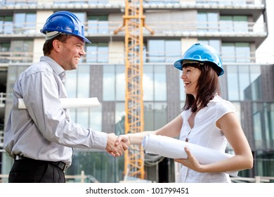 Happy construction specialists sealing the deal at a construction site