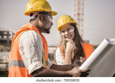 happy construction worker and civil engineer wearing safety jacket and helmet checking progress on blueprint.