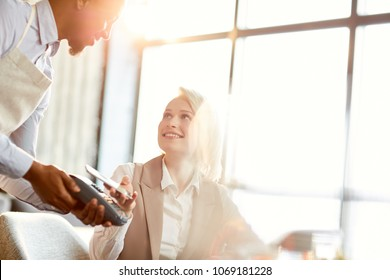 Happy contemporary woman looking at waiter while paying for order by her smartphone in cafe
