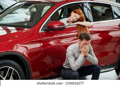 Happy content red-haired woman sits on driver seat in luxury car at car showroom, looking at herself at side mirrow while her sad boyfriend sits in the crouch outside covering his face by hands