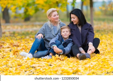 A happy, content same sex female couple and their son in a happy family theme with yellow fall leaves.