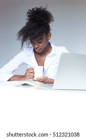Happy contented young African American woman with an afro hairstyle sitting at her desk in front of a laptop computer