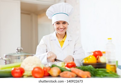 Happy  cook prepares vegetarian lunch  at commercial kitchen