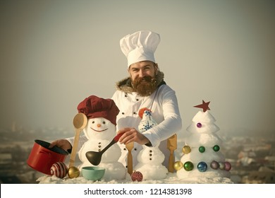 Happy cook, snowmen and snow xmas tree on blue sky. Cooking and diet concept. Hipster with ladle in white uniform. Man in chef hat ladling soup on winter day. Christmas and new year holidays food.