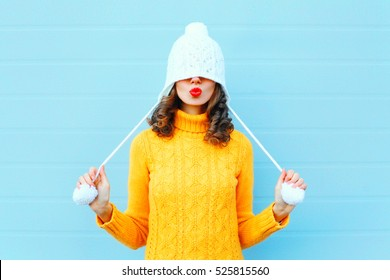 Happy, cooles Mädchen, das rote Lippen bläst, macht Luftkuss mit einem Strickhut, gelber Pullover auf blauem Hintergrund