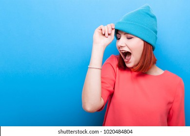 Happy cool hipster woman with her mouth open wearing a blue hat on blue background