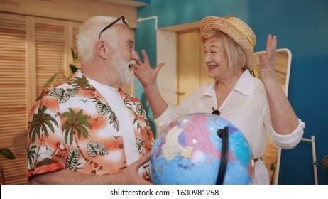Happy cool old couple smiling, talking about travel destinations, looking at globe, going fly together to foreign country. Tourist, adventures. Indoors. Rest, weekends.