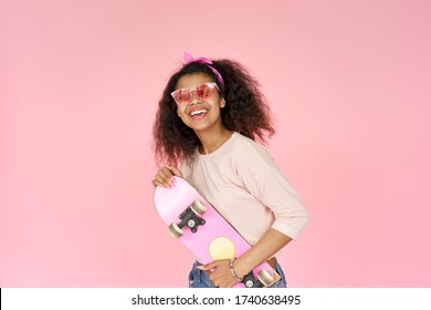 Happy cool smiling young african american teen gen z girl skater wearing sunglasses holding skateboard looking at camera posing with skate in hands isolated on pink studio background, portrait.