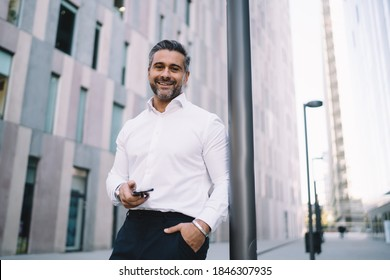Happy corporate director in formal white shirt holding cellphone gadget in hand and smiling at camera, half length portrait of successful middle aged employee with smartphone posing in downtown
