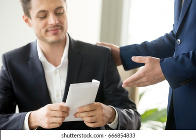 Happy corrupted businessman accepting bribe, male hand giving smiling office worker envelope salary at workplace, receiving business letter, bonus for good work, bribery and corruption concept