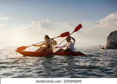 Happy coulple walks by sea kayak or canoe at sunset bay. Kayaking or canoeing concept with people