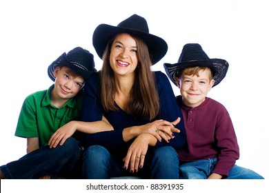 A happy, country family with cowboy hats.  Cute boys and a pretty Mom.