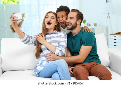 Happy couple with adopted African-American boy taking selfie on couch at home