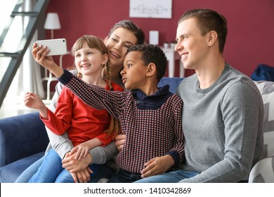 Happy couple with adopted children taking selfie at home