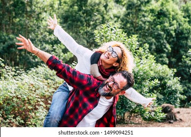 Happy couple of adult people caucasian man and woman have fun together in outdoor leisure activity in the nature- environment and love or forest concept with playful and youthful hipsters traveler