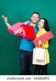 Happy couple after shopping. Pretty girl or beautiful woman, young, sexy, cute, fashion, brunette model with bags hugs handsome man on green wall