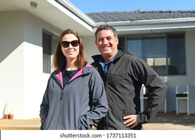 Happy couple (age 35-45) in winter clothing standing in front of new home. Buy, sell, real estate, property, home insurance, mortgage, bank loans and housing market concept. Real people. Copy space