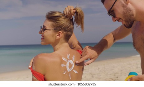 Happy couple applying sun tanning lotion on the beach, man putting sunscreen suntan cream on woman