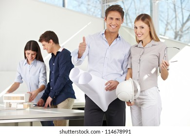 Happy couple in architecture office with blueprints holding thumbs up