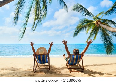 Happy couple with arms up relax on the beach enjoy beautiful sea on the tropical island. Summer beach vacation concept