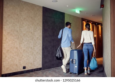 Happy couple arriving at hotel lobby with suitcase