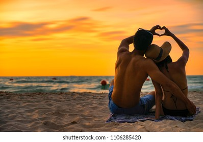 Happy couple asian in love having romantic tender moments at sunset on the beach