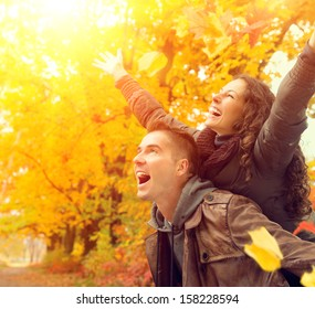 Happy Couple in Autumn Park. Fall. Young Family Having Fun Outdoors. Yellow Trees and Leaves. Laughing Man and Woman outside. Freedom Concept.