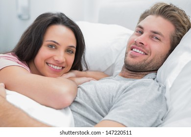 Happy couple awaking and looking at camera in bed