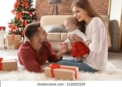 Happy couple with baby celebrating Christmas together at home