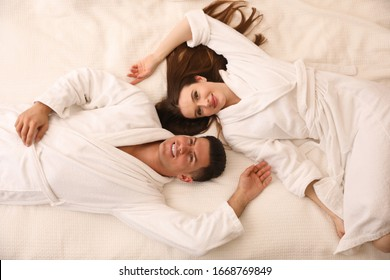 Happy couple in bathrobes lying on bed, top view