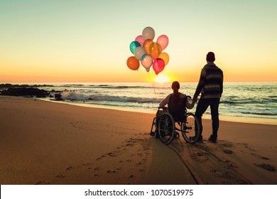 Happy couple at the beach, where woman is on a wheelchair holding balloons on her hands