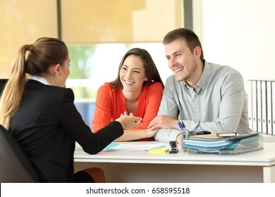 Happy couple being attended by office worker at office