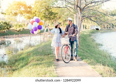 Happy couple with bicycle against the autumn background park. Filtered image.