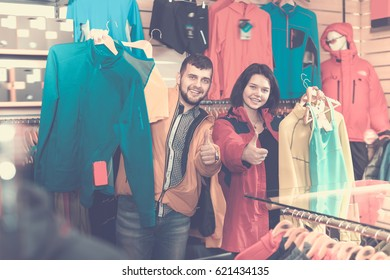 Happy couple boasting various sportswear items in sports clothes store