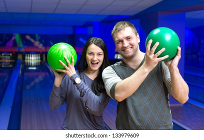 Happy couple in a bowling alley having fun