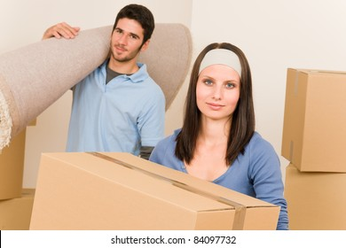 Happy couple with boxes and carpet moving into new home