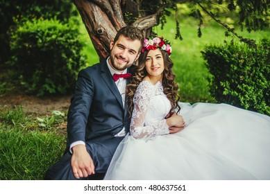 Happy couple, bride & groom hugging near old tree