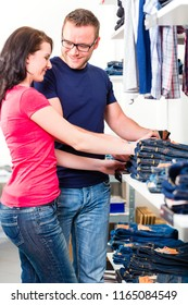 Happy couple buying blue jeans in shop or store
