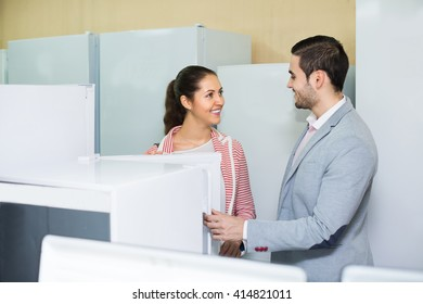 Happy couple buying domestic refrigerator in supermarket