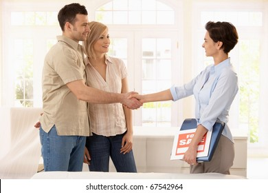 Happy couple buying new home, shaking hands with estate agent.?