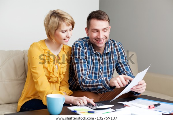 Happy couple calculating bills sitting sonf sofa in living room
