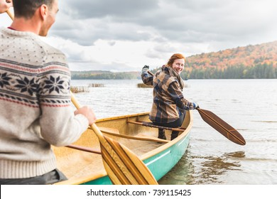 Happy couple canoeing in a lake in Canada. Trees on background with colourful leaves during autumn. Young and happy, enjoying a canoe trip together. Wanderlust and nature concepts.