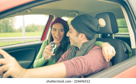 happy couple in the car. girlfriend is singing while man is driving. concept of happiness and carefree