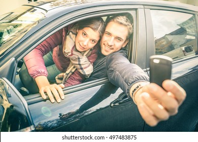 Happy couple at car rent showing electronic key ready for the next road trip - Transportation and vehicle loan concept with satisfied people at rental service - Soft backlighting and desat filter