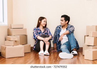 Happy couple with cardboard box at new home