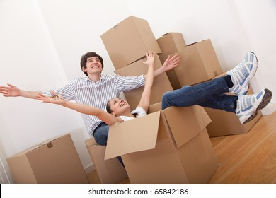 Happy couple with cardboard boxes moving to a new house